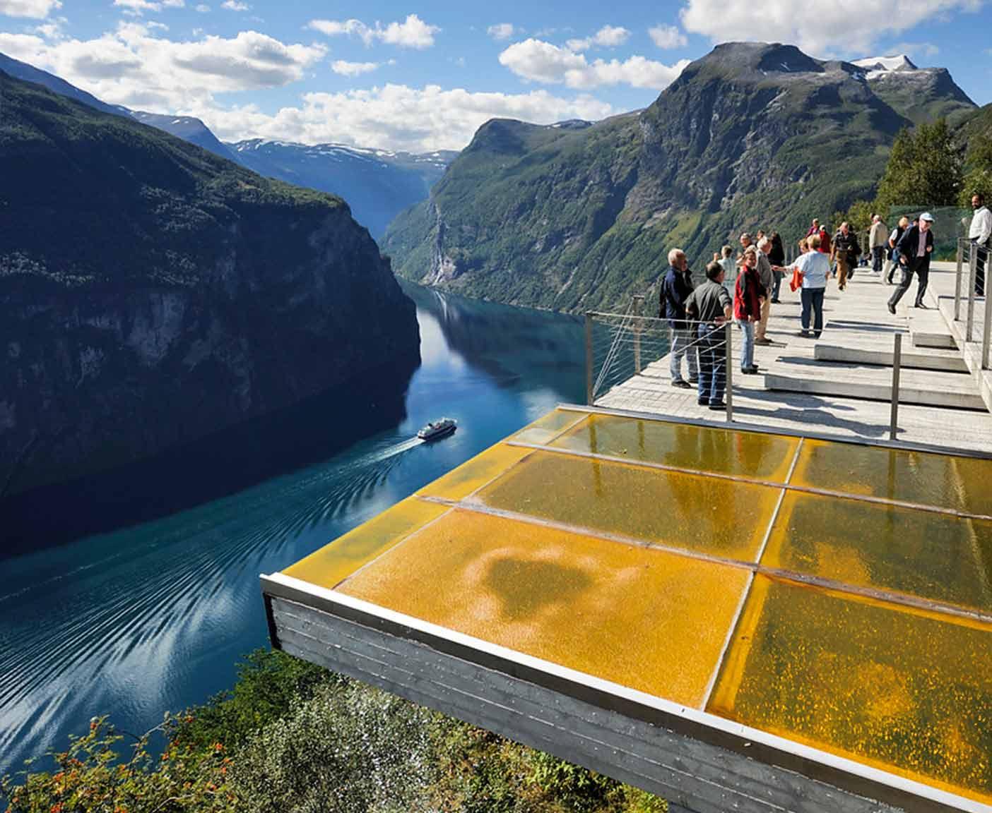 Aussichtsplattform Stegastein in Norwegen am Geirangerfjord Menschen auf einer Plattform Kreuzfahrtschiff auf dem Fjord und Berge im Hintergrund
