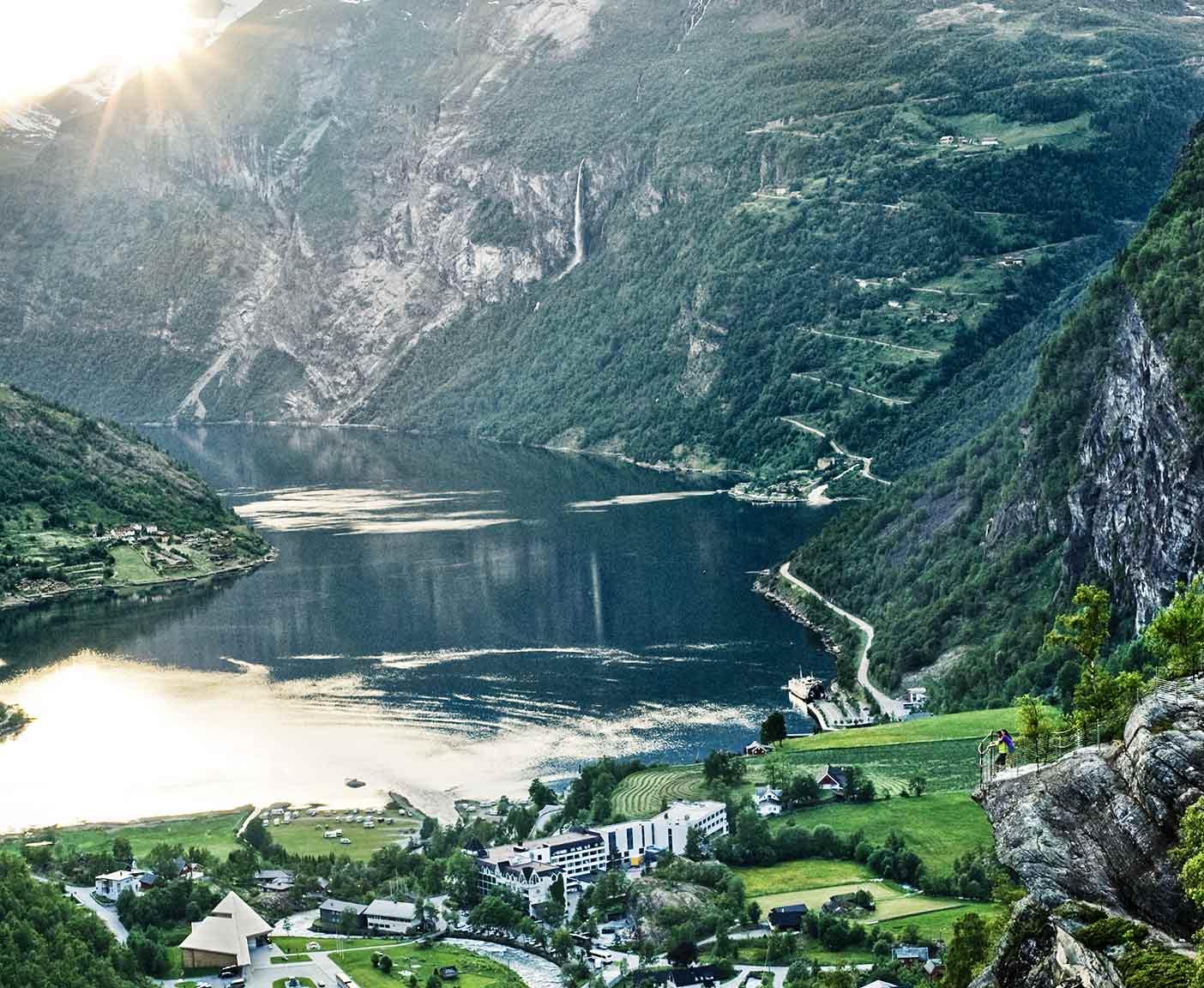 Sonnenstrahl scheint auf den Fjord, im tal das Dorf Geiranger und Berge im Hintergrund