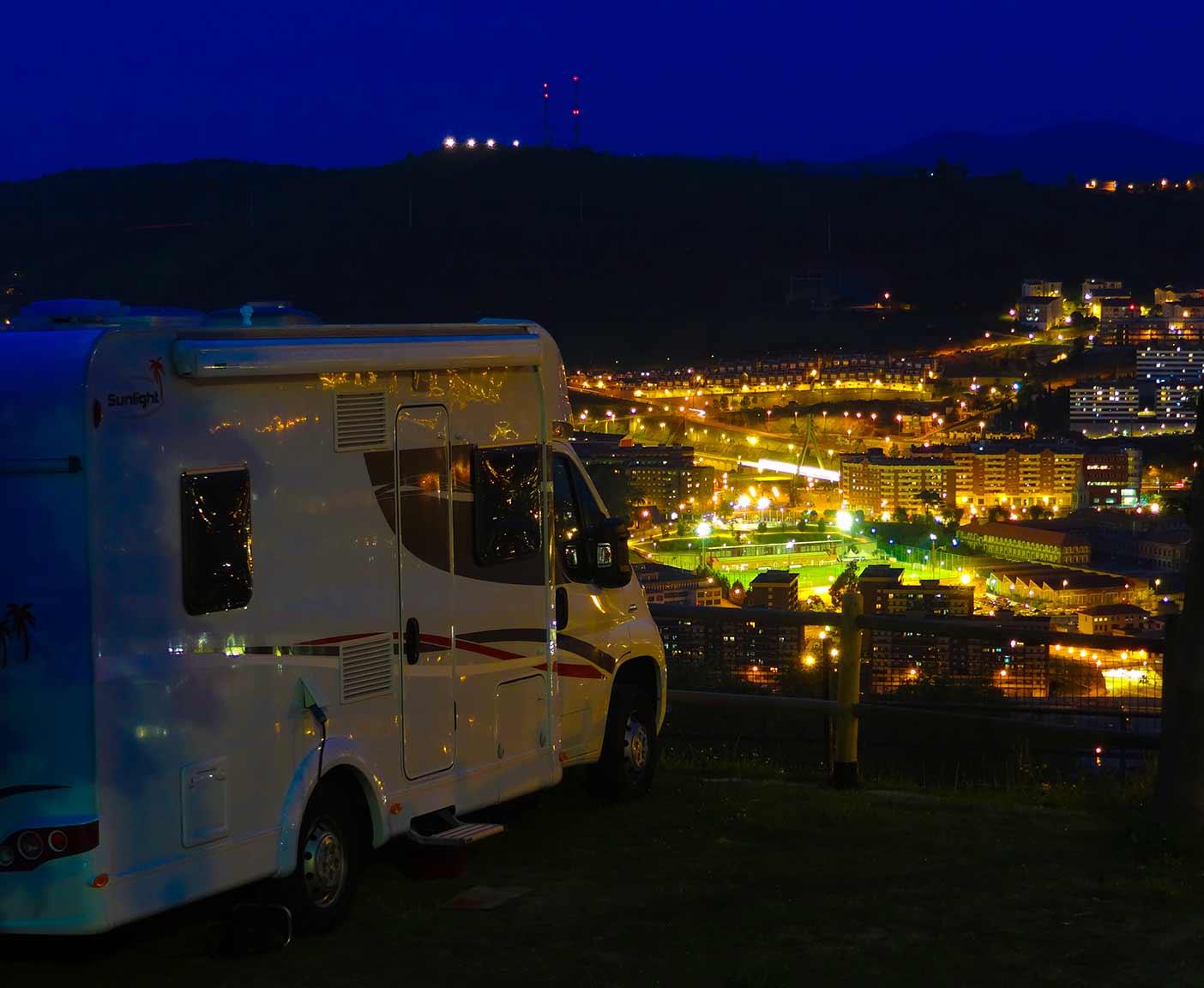 Wohnmobil in der Nacht, Lichter einer Stadt, Wohnmobil vermieten bei PaulCamper