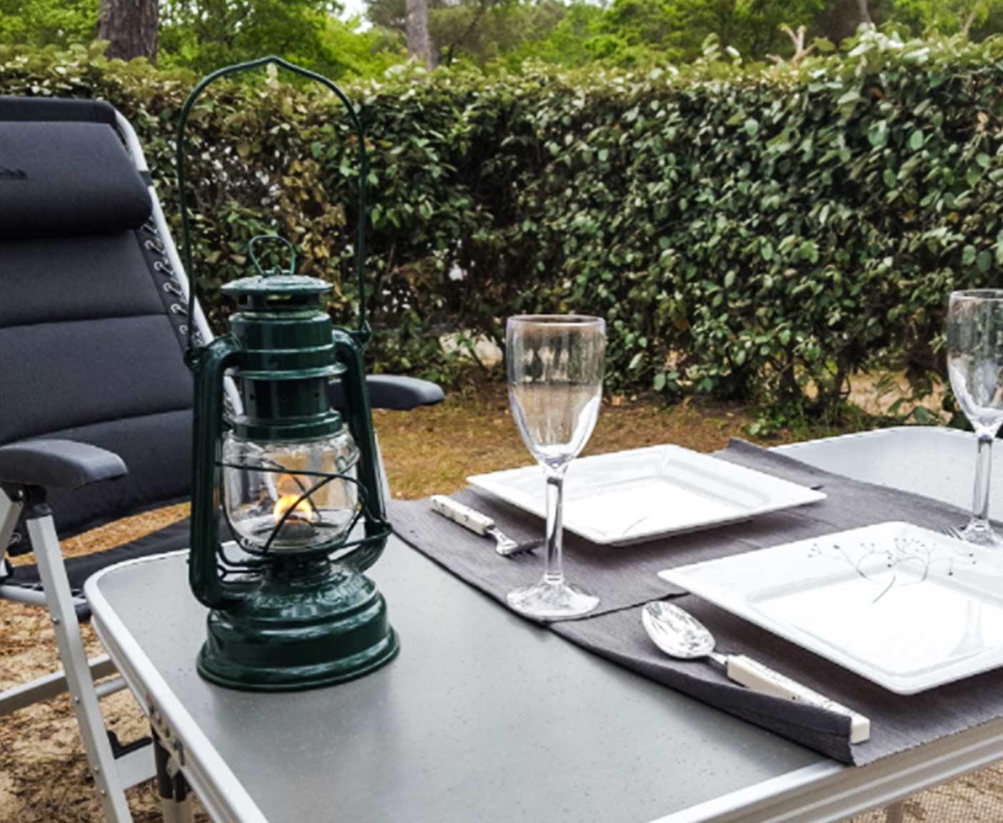 Campingstuhl und Campingtisch, kleine Laterne, Weingläser und Geschirr auf dem Tisch, Wohnmobil vermieten bei PaulCamper