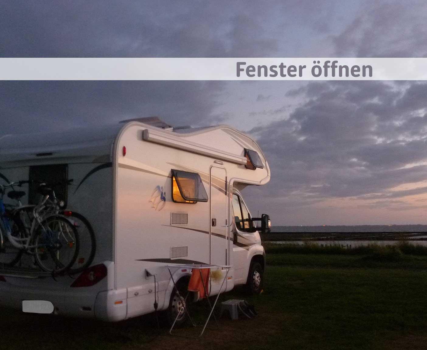 Wohnmobil mit geöffnetem Fenster vor Meer und dunkelblauem Himmel nach dem Sonnenuntergang