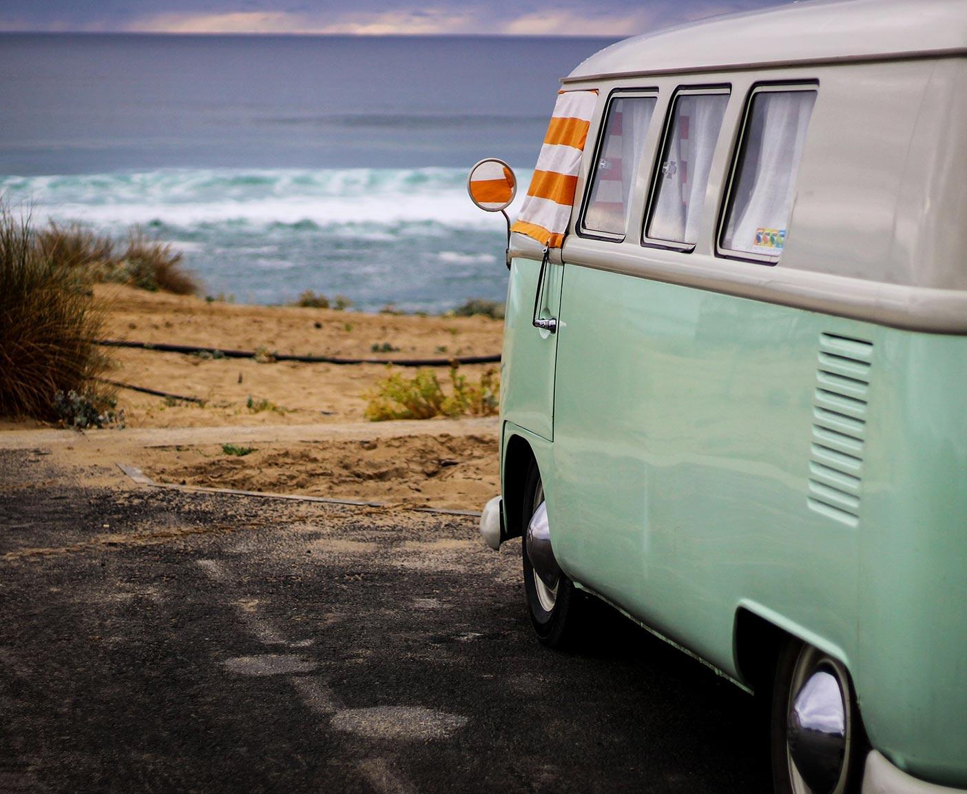 VW Camper in hellblau steht an der Küste am Strand, orange-weiße Handtücher hängen als Sonnenschutz in den Fenstern