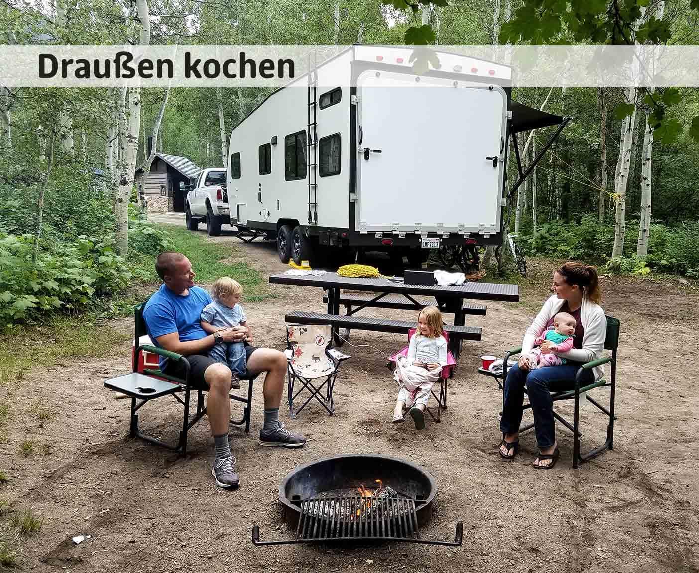 Familie mit zwei Kindern kocht bzw. grillt draußen in der Natur, sie sitzen vor ihrem Wohnmobil