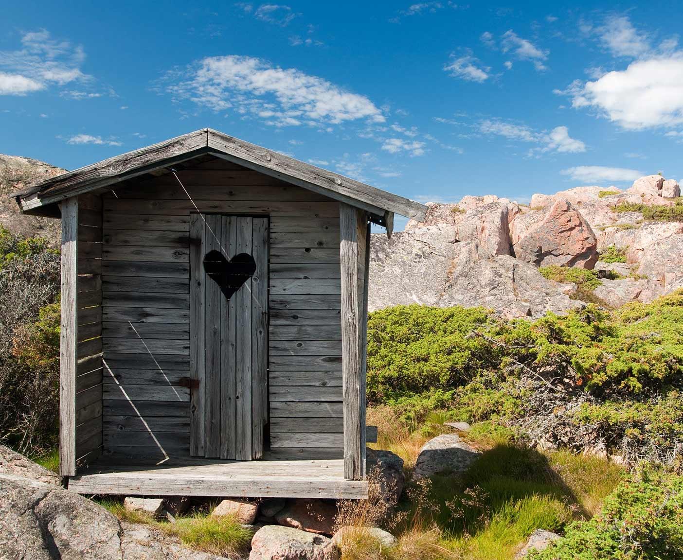 Klohaus aus Holz mit Herz eingeschnitzt in einer schönen Berglandschaft in der Natur, Campingtoiletten PaulCamper