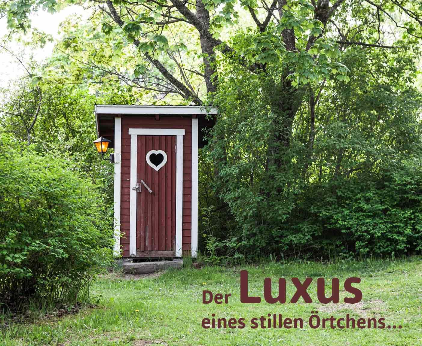 Toilettenhaus aus Holz mit Herz und Laterne im Grünen in der Natur, Der Luxus eines stillen Örtchens, Campingtoilette PaulCamper