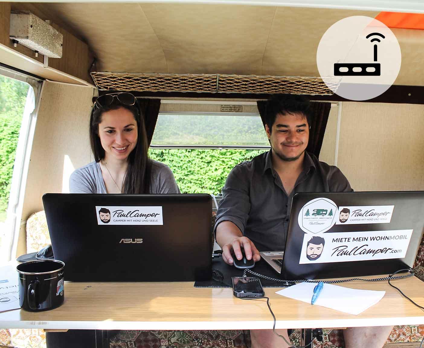 Internet im Wohnmobil, Frau und Mann arbeiten an ihren Laptops im Wohnwagen, PaulCamper, Router