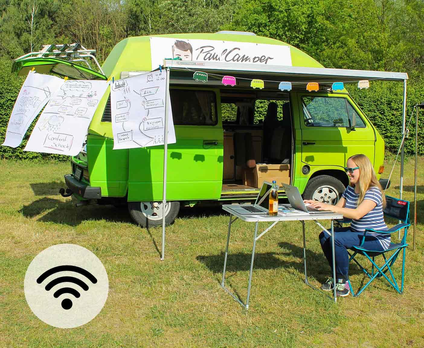 Internet im Wohnmobil, Frau sitzt draußen vor dem Wohnmobil am Laptop und arbeitet, grüner Camper, WLAN, PaulCamper