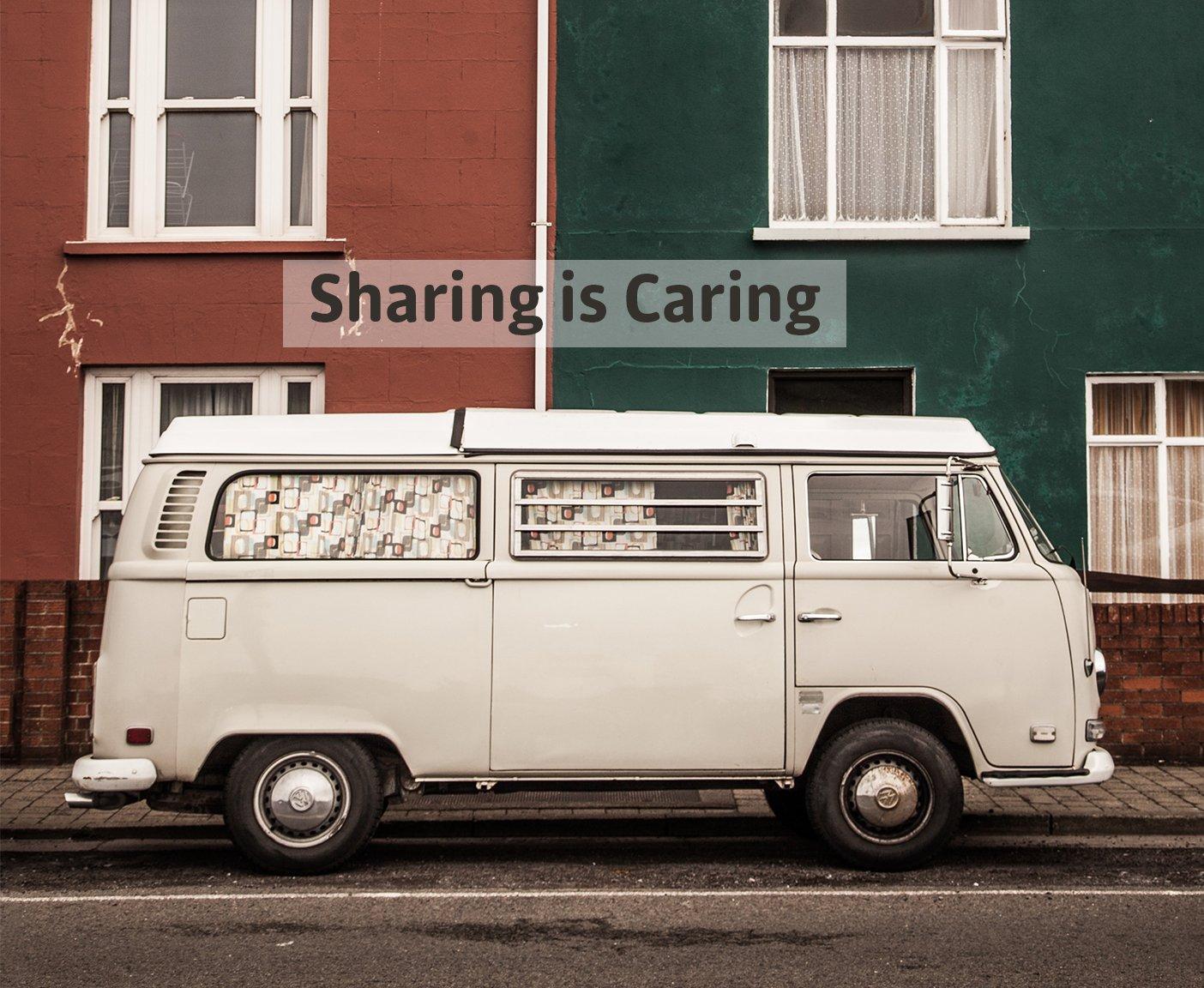 VW-Bus vor zwei Haeusern, Sharing is Caring Aufschrift