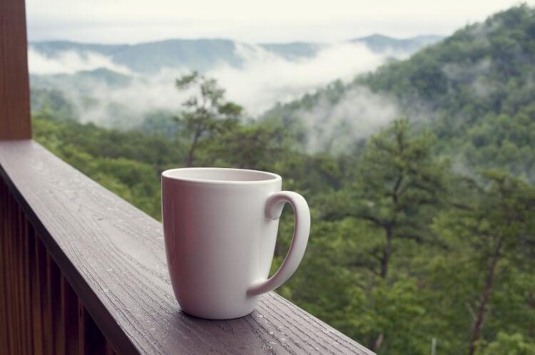 Porzellan Tasse auf Veranda mit Aussicht Wald und Berg