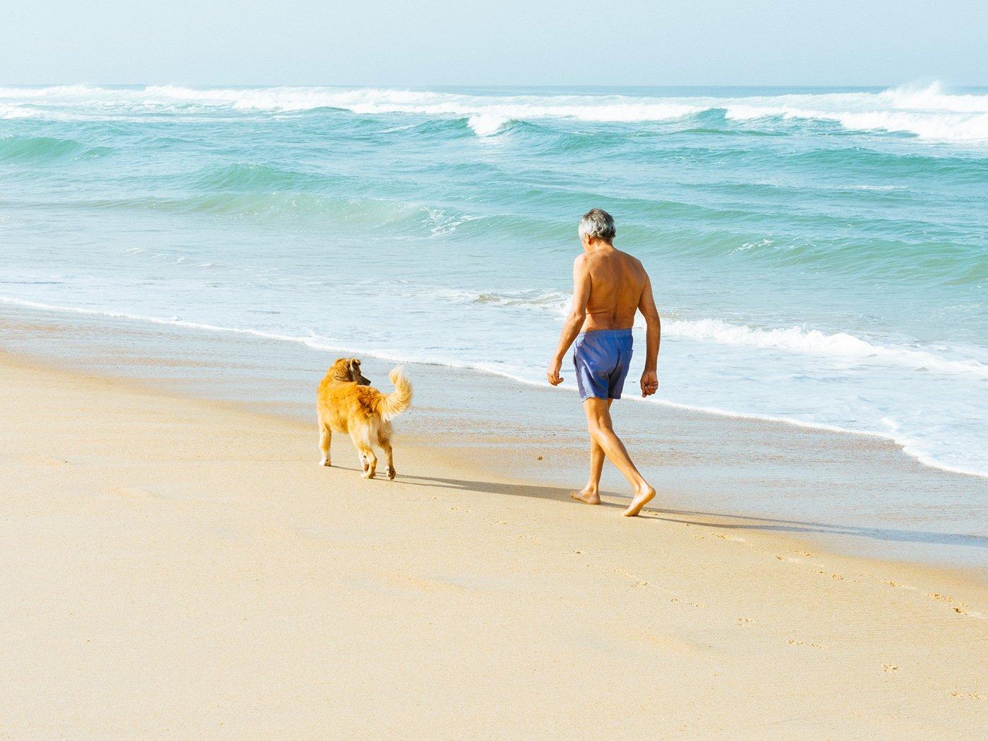 Urlaub mit Hund: Mann am Strand
