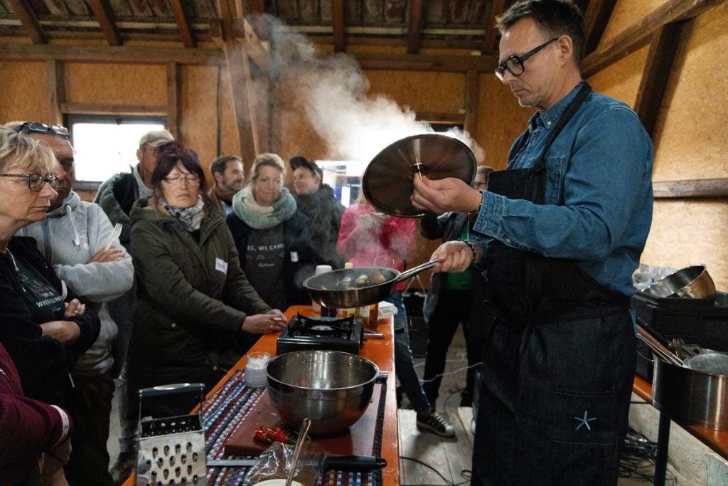 Holger Stromberg öffnet einen dampfenden Kochtopf