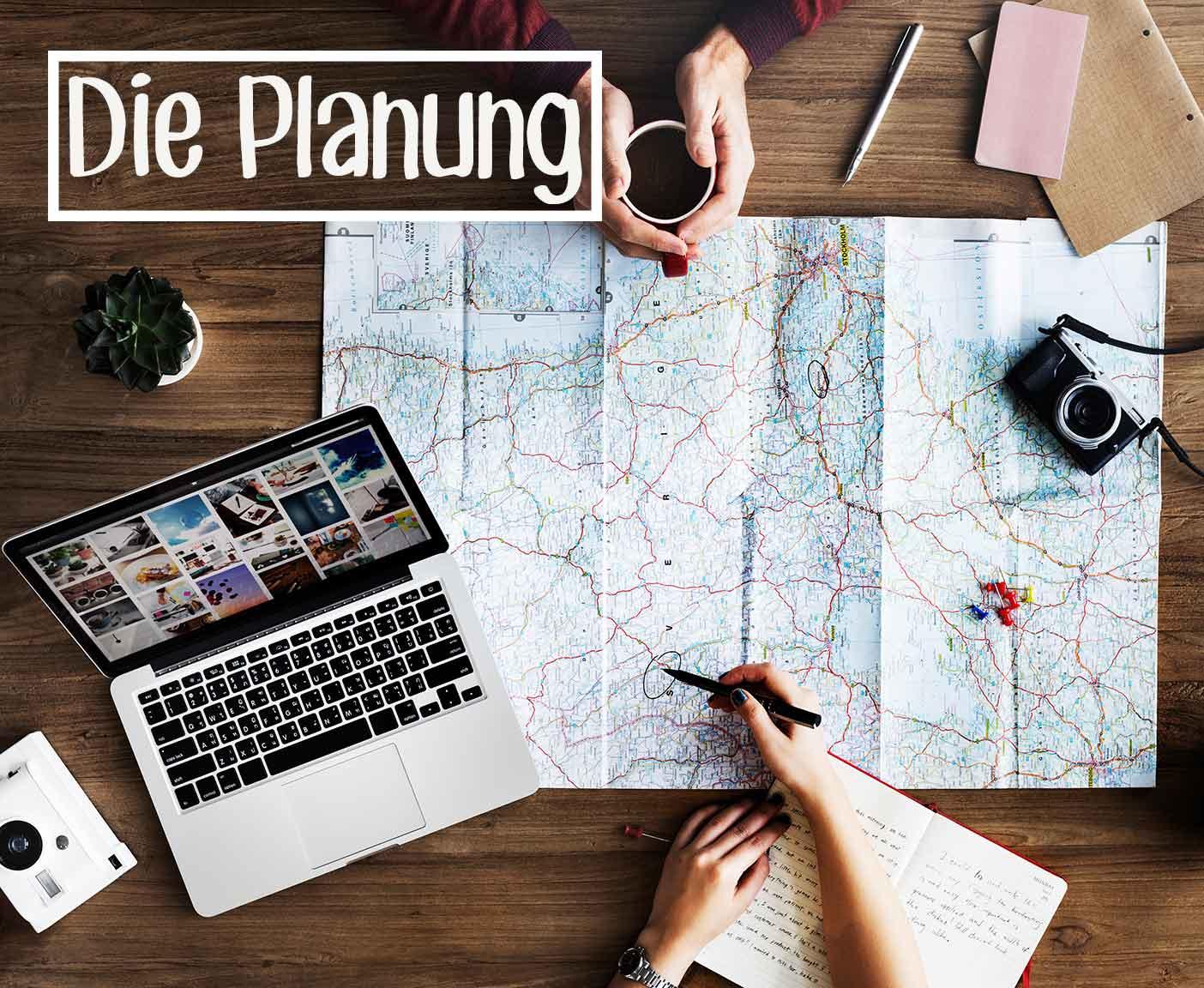 Karte auf dem Tisch mit Laptop Kamera und Kaffee Reiseplanung mit PaulCamper