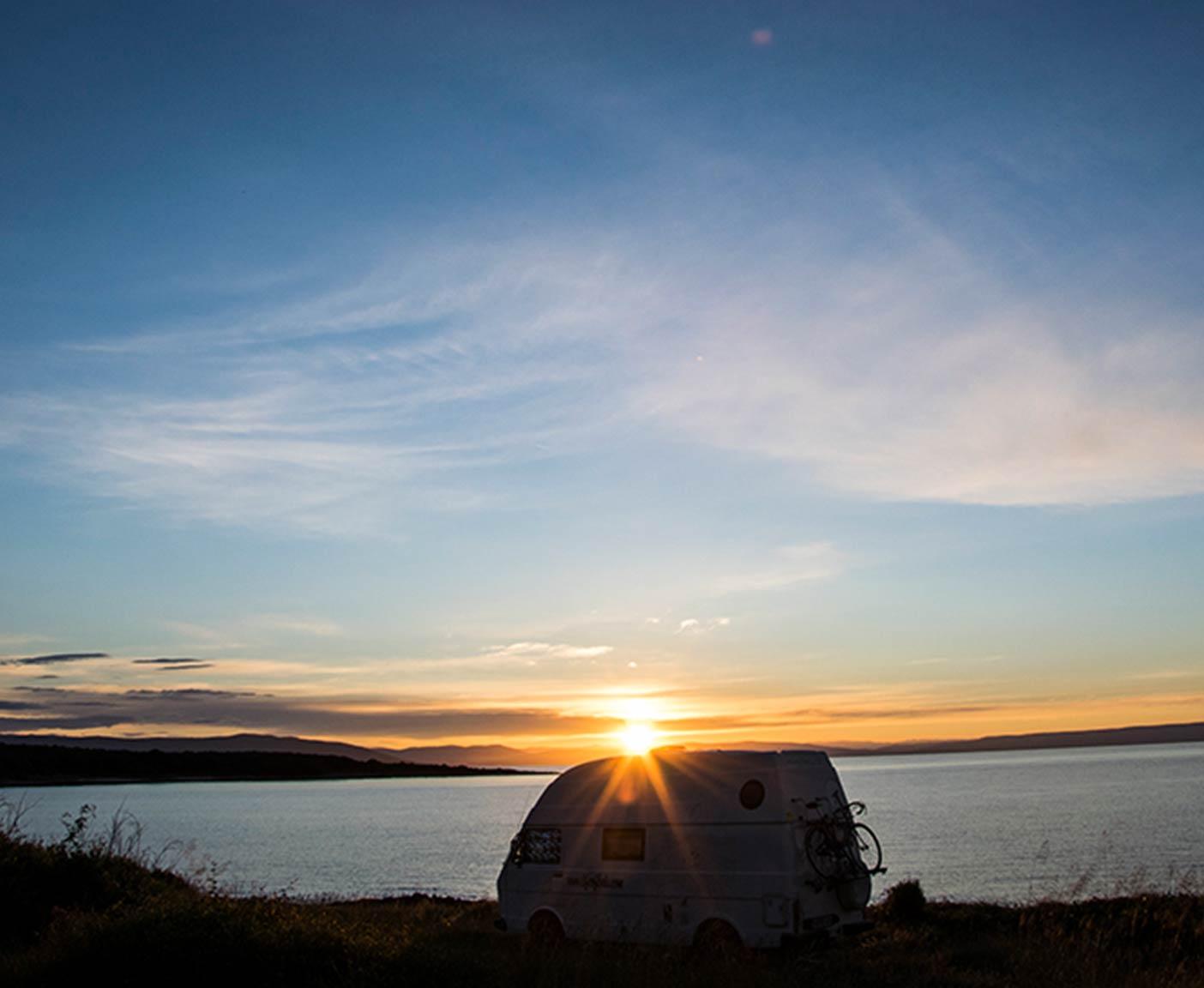 Camper am See im Sonnenuntergang