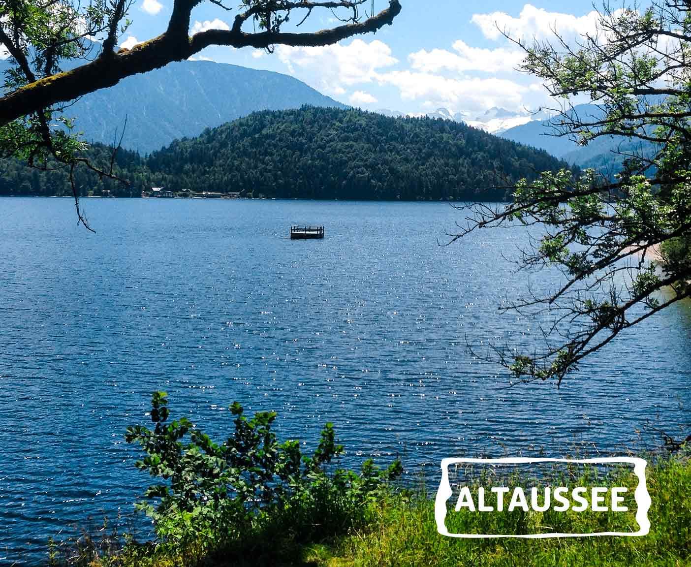 kleines Boot schwimmt in der Mitte vom Altaussee, blaues Wasser, umgeben von Bäumen und Wiese, PaulCamper an den Seen in Österreich