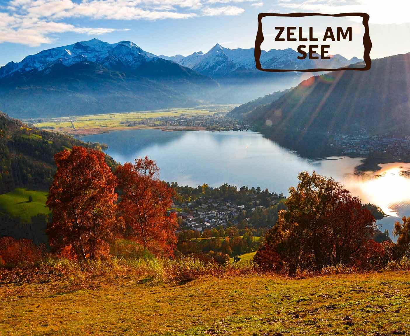 rote Bäume und Büsche stehen vor Zell am See, Berge mit Eisspitzen im Hintergrund, Sonnenstrahl, Flare, PaulCamper an den Seen in Österreich